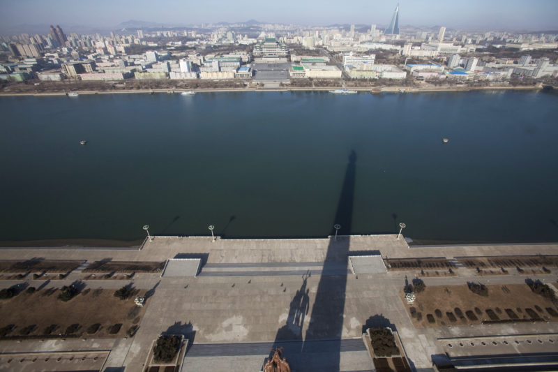 David Guttenfelder – A shadow of the 170-meter (560-foot) Juche Tower is cast over the Taedong River in Pyongyang, North Korea