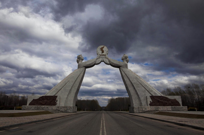 David Guttenfelder – A statue known as the Monument to the Three Charters for National Reunification, which symbolizes the hope for eventual reunification of the two Koreas, arches over a highway at the edge of Pyongyang, North Korea