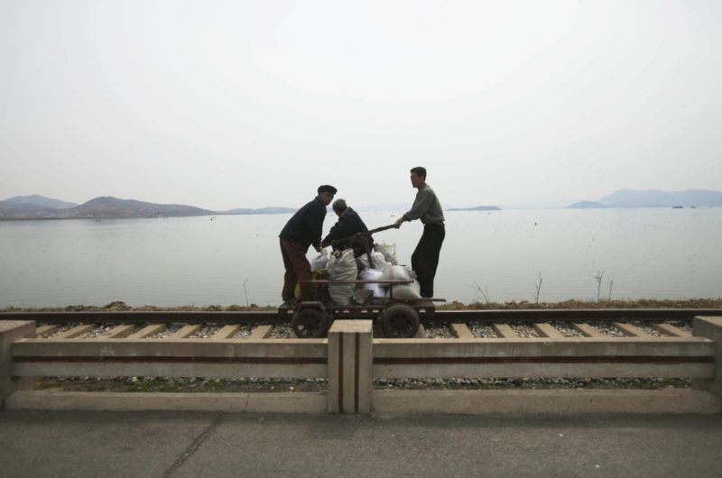 David Guttenfelder – In this April 21, 2011 photo, men operate a manual rail car on tracks running along the West Sea barrage near Nampho, North Korea