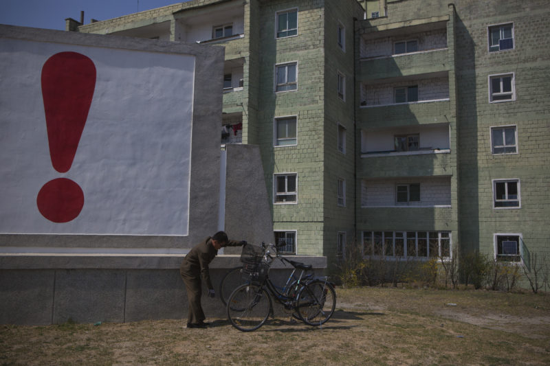 David Guttenfelder - A North Korean man checks his bicycle next to a painted exclamation point on a propaganda billboard on Wednesday April 24, 2013 in Kaesong, North Korea, north of the demilitarized zone which separates the two Koreas