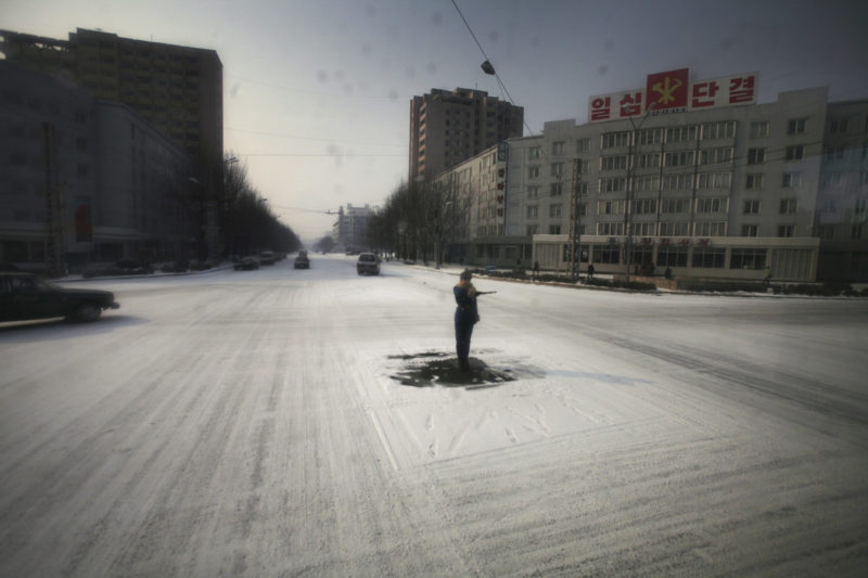 David Guttenfelder - A traffic guard goes through the motions in the capital of Pyongyang, where streets are almost empty of cars