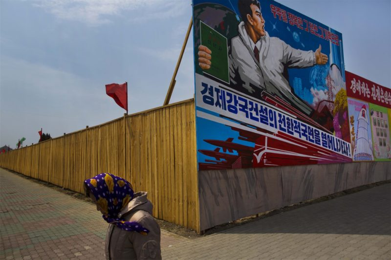 David Guttenfelder - A woman in Pyongyang walks past a billboard advertising North Korea's missile prowess. The capital city is rife with stylized propaganda