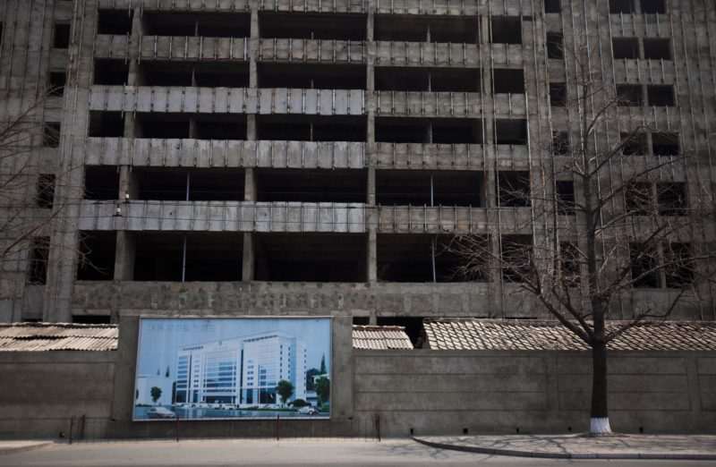 David Guttenfelder - In this April 13, 2011 photo, an illustration of a building project hangs in front of the construction project in progress in Pyongyang, North Korea
