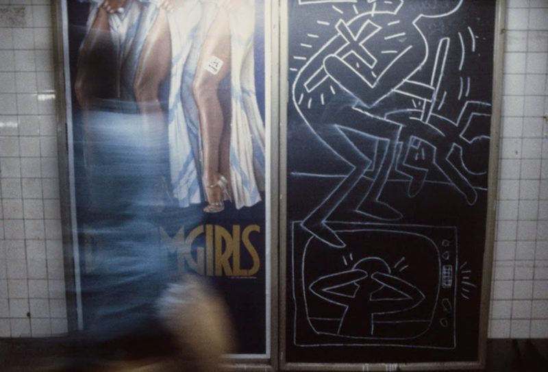 Christopher Morris - A commuter walks by a poster for the musical Dreamgirls and a Keith Haring chalk drawing, 1981