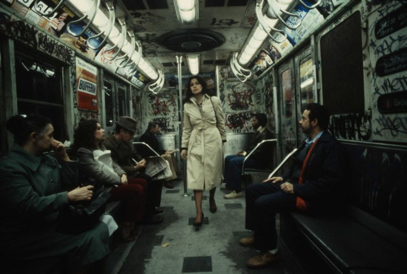 Christopher Morris - A woman walks through a heavily graffitied subway car, 1981