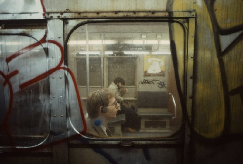Christopher Morris - A man is seen wearing headphones through a subway car window, 1981