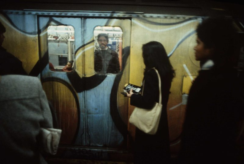 Christopher Morris - A woman waits to board a train pulling into a station, 1981. Graffiti on the outside of subway cars was usually more elaborate than that inside