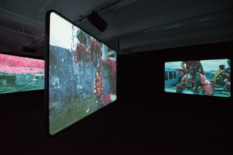 Richard Mosse - Installation view, The Enclave, 2012–2013. 16 mm infrared film transferred to HD video. Produced in eastern Democratic Republic of Congo. Courtesy of Jack Shainman Gallery, New York