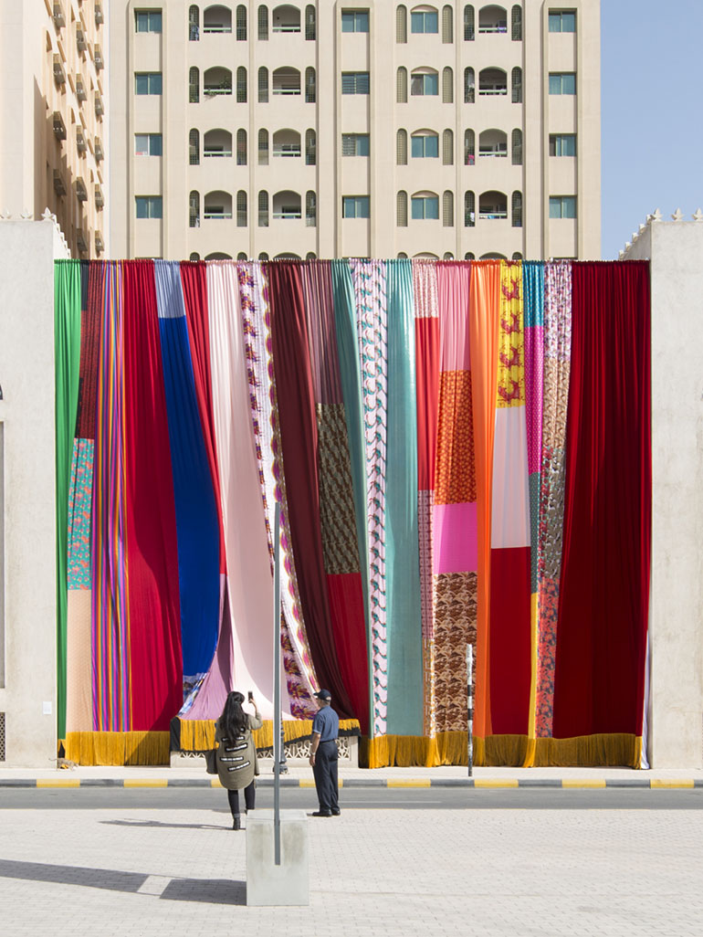 Joe Namy's colorful & oversized curtain partly covers museum