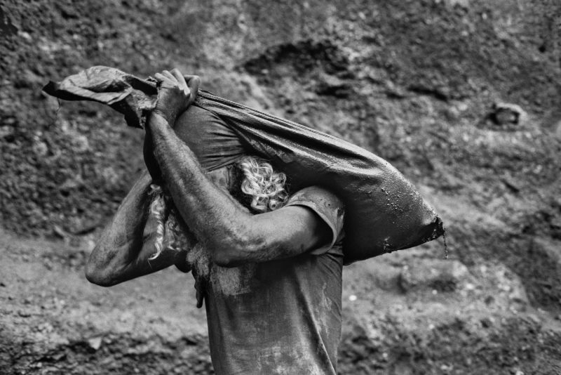 Sebastiao Salgado – Serra Pelada Gold Mine, Brazil, 1986, A worker carries a sack of dirt out of the mine