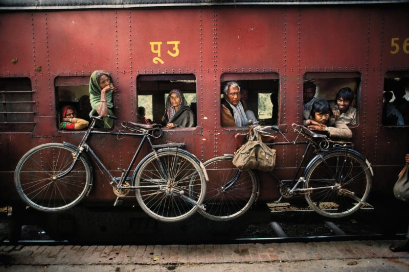 Steve McCurry - Bicycles hang on the side of a train traveling from Dacca to Peshawar, West Bengal, India. April 1993