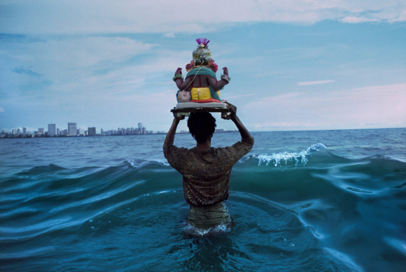 Steve McCurry - Man carrying statue of Ganesh into the Indian Ocean, Mumbai, India, 1993