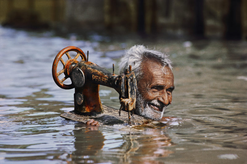 Steve McCurry - Tailor carries his sewing machine through monsoon floodwaters