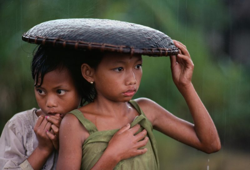 Steve McCurry - Indonesia. Java. 1983, Girls huddle under a rice basket to escape the rain