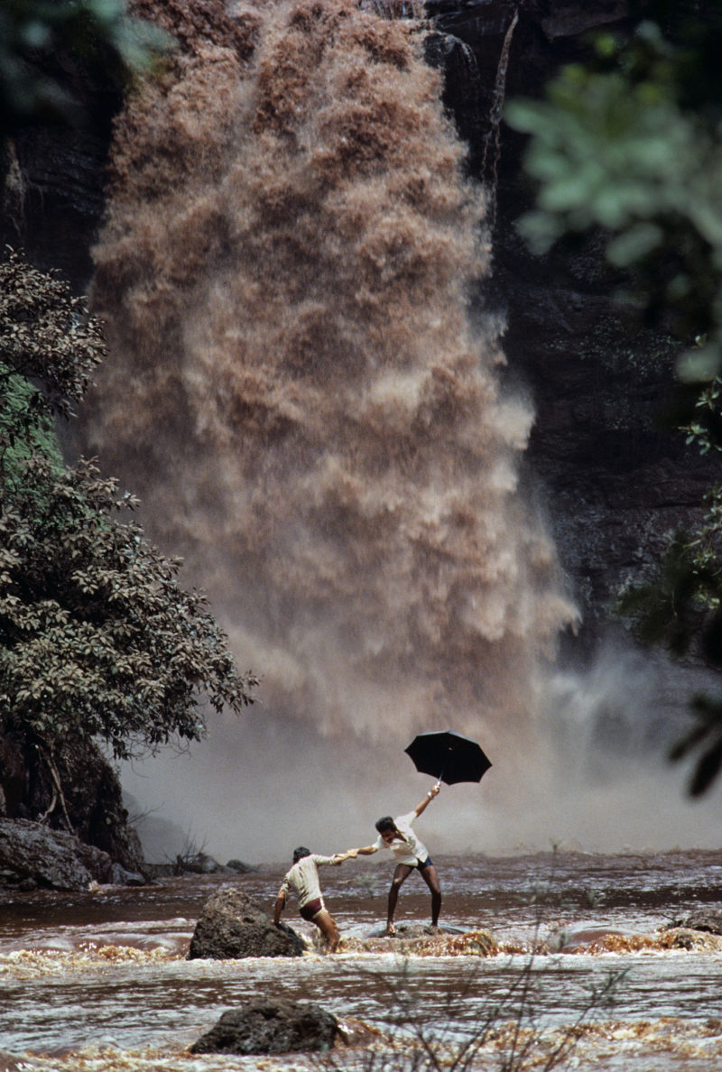 Steve McCurry - Two men crossing a swollen river after the bridge was washed away, Goa, India