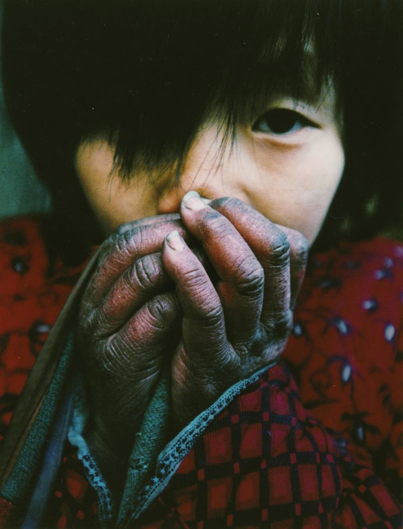 Lu Guang - A young girl warms her hands in winter. Her father is infected with HIV and still cares for five children and his elderly parents