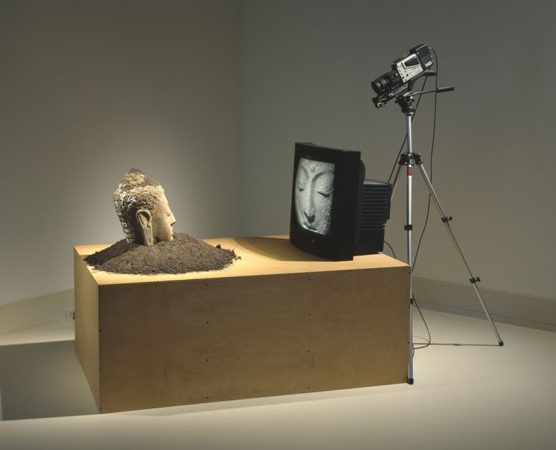 Nam June Paik – Buddha Watching TV, 1974/1997, Stone sculpture, soil, closed-circuit video camera, video monitor, tripod, plywood base, Virginia Museum of Fine Arts