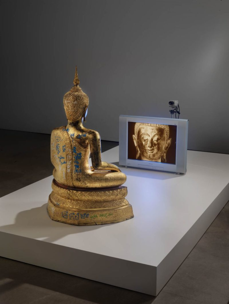 Nam June Paik - Golden Buddha, 2005, closed-circuit video (color) with television and wood Buddha with permanent oil marker additions, 46 1/2 × 106 × 31 3/4 inches (118.1 × 269.2 × 80.6 cm)