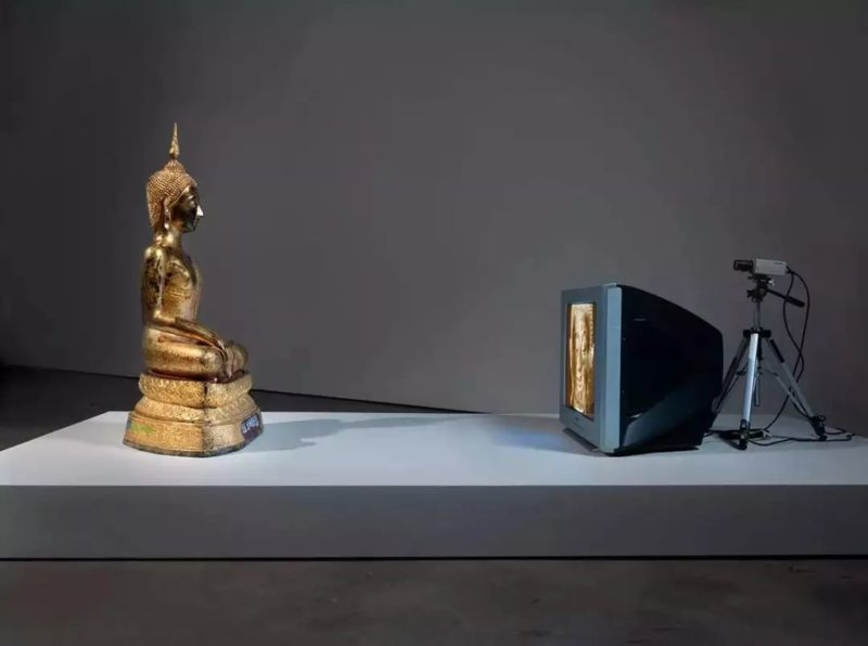 Nam June Paik - Golden Buddha, 2005, closed-circuit video (color) with television and wood Buddha with permanent oil marker additions, 46 1:2 × 106 × 31 3:4 inches (118.1 × 269.2 × 80.6 cm)