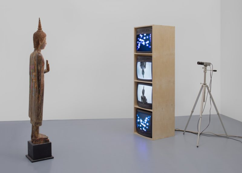 Nam June Paik - Standing Buddha with Outstretched Hand, 2005 Single-channel video (color, silent) with televisions, closed-circuit video (colour), and wood Buddha with permanent oil marker additions