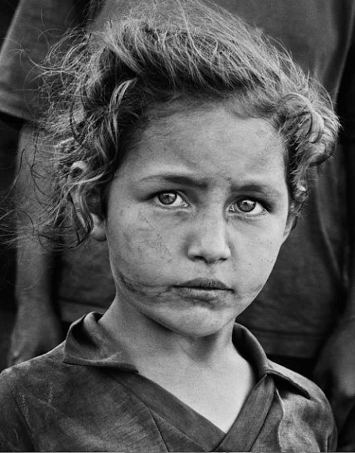 Sebastião Salgado - Little girl of landless family. More than 3,000 families have gathered at the edge of the national road while waiting for the occupation of land. Paraná, Brazil. 1996
