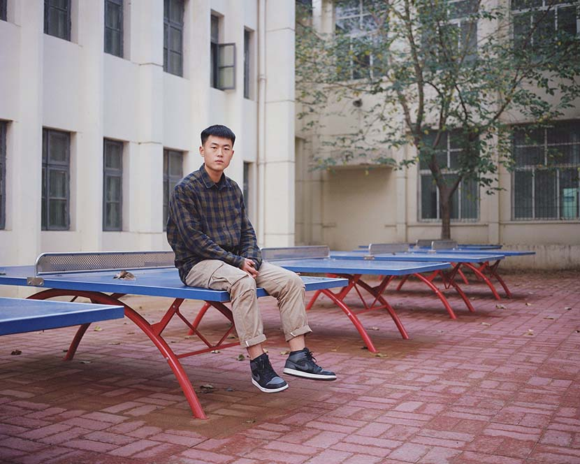 Shi Yangkun - Guo Tianlong, from Nanjie Village, sits on a pingpong table in Henan province, 2018