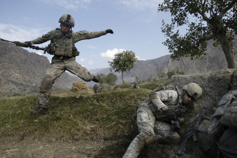 "David Guttenfelder – Afghanistan - Cpl. Casey Liffrig, left, leaps for cover as Lt. Thomas Goodman gets down as insurgent fighters ambush US soldiers during a patrol in the Pech Valley of the Kunar province, Nov. 3, 2009. ""A platoon of soldiers had gone to a nearby village to tell the elders to stop the insurgent from passing through to attack U.S. targets. The villagers said they just wanted to be left alone. They claimed they had asked the insurgent to stay away, and wished the Americans would do the same. About 500 yards outside the town they soldiers were ambushed and insurgent gunfire whistled down from the mountainside. Pinned down in an irrigation canal and a rice paddy with only small walls and terraces for cover, soldiers began bounding two-by-two across open fields to take cover. It took air support from helicopters, and artillery, and the soldiers fighting back for four hours before they could retreat to safety. At one point in the battle ammunition ran low. A helicopter hovered into a river bed and shoved out bullets and grenades on a medical stretcher for them to retrieve."""