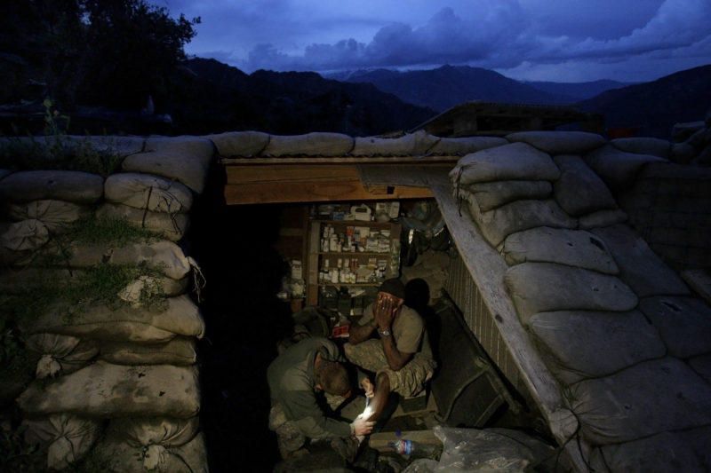 David Guttenfelder – Afghanistan - Spc. Cecil Montgomery of Many, LA, right, from the U.S. Army First Battalion, 26th Infantry is treated by medic Pfc. Dorian Biberdorf of Bellevue, NB, inside a medical bunker at firebase Restrepo in the Korengal Valley of Afghanistan's Kunar Province on Saturday, May 9, 2009. Montgomery's leg, which was gashed in an operation two weeks ago, became infected and a medic had to open the wound to try to remove the infection and sterilize it.