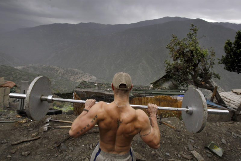 David Guttenfelder – Afghanistan - Spl. Taylor Jordan from the U.S. Army First Battalion, 26th Infantry lifts weights in the rain at his platoon's base Camp Restrepo in the Korengal Valley in Afghanistan's Kunar Province on Friday May 8, 2009