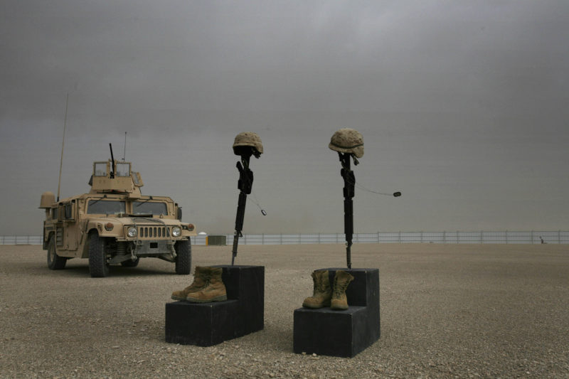 David Guttenfelder – Afghanistan - The helmets, weapons, dogtags and boots of two fallen U.S. Marines stand alone at the end of a ceremony in their honor at Camp Bastion, in southern Afghanistan Tuesday, April 22, 2008. 1st Sgt. Luke Mercardante, 35, of Athens, Ga, and Cpl. Kyle W. Wilks, 24, of Rogers, Ark. died on April 15 when their vehicle struck a roadside bomb in. Both were assigned to the Combat Logistics Batallion, 24th Marine Expeditionary Unit.