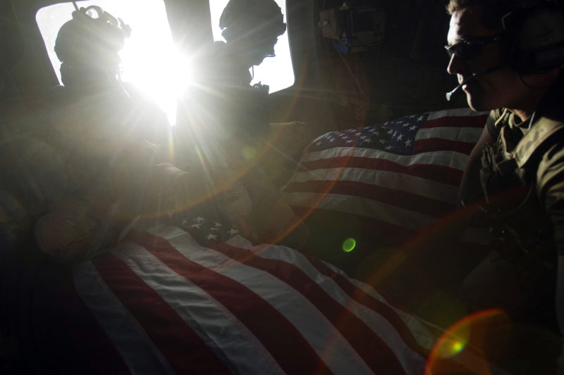 David Guttenfelder – Afghanistan - U.S. Air Force pararescuemen ride in the back of their helicopter on Oct. 10 with the flag-draped bodies of American soldiers