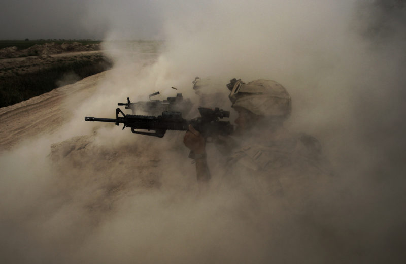 "David Guttenfelder – Afghanistan - U.S. Marines, from the 24th Marine Expeditionary Unit, return fire on insurgent positions near the town of Garmser in Helmand Province, May 2, 2008. ""During an air assault into Helmand River Valley, they came under rocket and small arms fire while they occupied a small farm compound. Several guys returned fire from behind the cover of a hard-packed dirt berm. Their gun fire was so intense that the recoils or concussions of their own weapons caused the berm to rise up into a huge dust cloud. The squad's first sergeant started screaming for them to cease fire because none of them could see down range any longer. I shot several photos. In the first few you see at least eight or 10 Marines shooting in a line on the hill. Seconds later, when I took this photo, I could only see part of two men, and one of the brass cartridges ejecting from the M-4 and up into the dust cloud."""