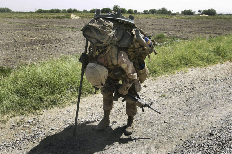 David Guttenfelder – Afghanistan - US Marine Cpl. Brian Knight, of Cincinnati, Ohio, pauses briefly in the heat to rest with his heavy pack filled with mortar equipment, ammunition, food, and water