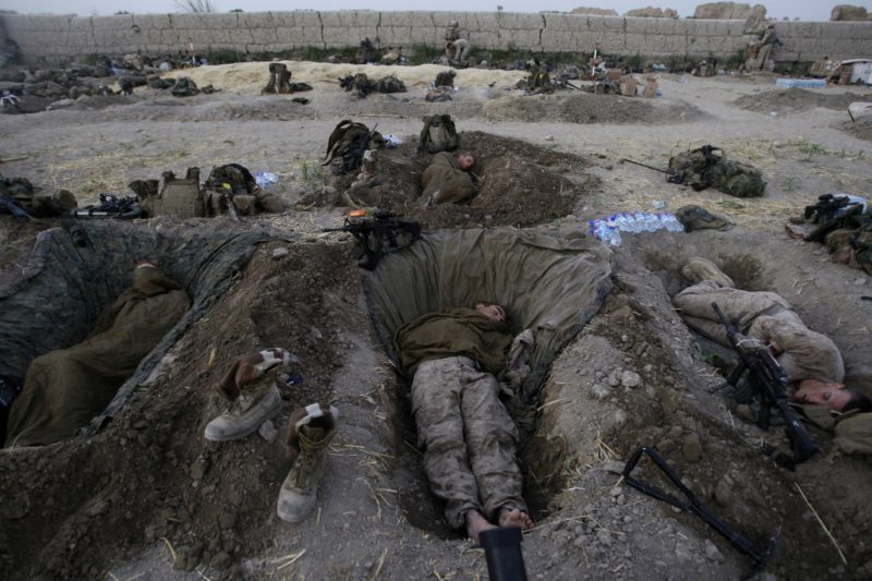 "David Guttenfelder – Afghanistan - US Marines from the 2nd Marine Expeditionary Brigade sleep in their fighting holes inside a compound where they stayed for the night, in the Nawa district of the Helmand province, July 8, 2009. ""In July, the US Marines launched a 4,400-Marine air assault into Afghanistan's Helmand province. It was part of what we were all calling 'Obama's Surge,' the first troops who would have the new president's signature at the bottom of their deployment papers. The unit I was attached to was sent to the northern part of the province to an area where NATO troops had never gone. ""Most soldiers and Marines, when they come to Afghanistan, are sent to a pre-existing combat outpost so they already have a base to return to most every night. But these guys literally stepped off a helicopter in the middle of the night, in a hostile area, and started walking and looking for a home. It was more than 120 degrees. We walked as far as 10 miles a day for well over a week and carried all of our gear, food and water on our backs. And every night we made camp wherever we could. On the sixth night of the operation, we made camp inside a large mud-walled farmers field. Everyone dropped their heavy packs. The area was very open and vulnerable to mortar attacks so they guys were told to begin digging in the dark to make firing positions where each man would sleep for the night. I had to borrow a small collapsible spade from one of the Marines to dig my own grave-sized bed. It was too dark to make photos that night, and I was busy digging my own hole. I woke before dawn so I could make this photograph of the guys while most were still sleeping. The Marines paid rent to the farmer and damages to the field."""