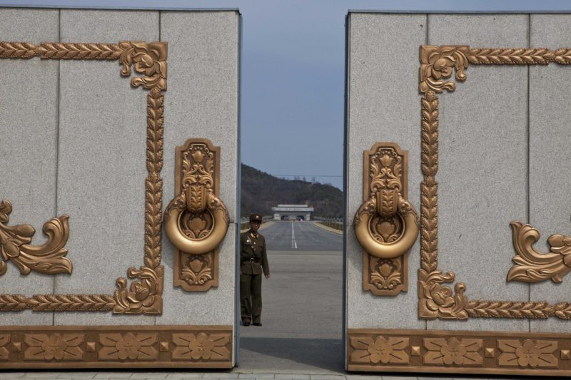 David Guttenfelder - A North Korean soldier guarding the entrance to Pyongyang's Kumsusan mausoleum, where the bodies of the late leaders Kim Il Sung and Kim Jong Il lie embalmed, looks back through the doors of the main gate Monday, April 15, 2013