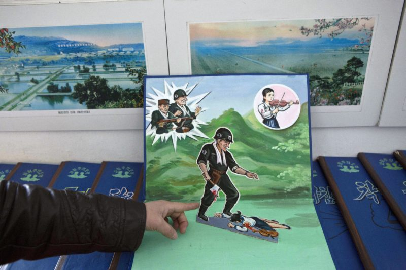 A North Korean teacher holds open a children's pop-up book, which depicts a U.S. soldier killing a Korean woman with a hatchet, in a library room at Kaeson Kindergarten in central Pyongyang on Saturday, March 9, 2013. For North Koreans, the systematic indoctrination of anti-Americanism starts as early as kindergarten.