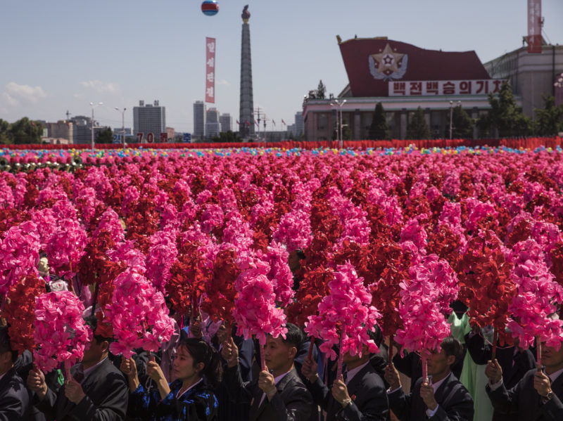 """David Guttenfelder - North Korean civilians wave pink and red artificial flowers and chant """"Kim Jong Un"""" on Kim Il Sung Square in Pyongyang during a mass military parade to mark its 70th anniversary as a nation"""