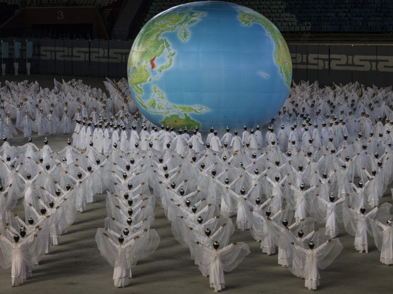 David Guttenfelder - North Korean women gather around a globe with a unified Korean Peninsula depicted on the map on the field of the May Day Stadium