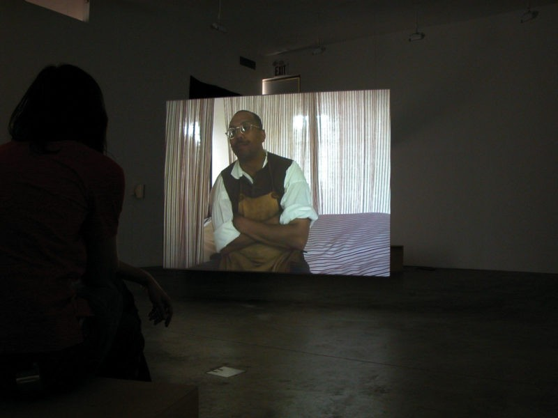 Omer Fast - Godville, 2005, Two channel video installation, 50 minutes, Installation view, Postmasters Gallery, New York