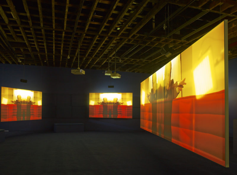 Simon de Pury in Isaac Julien's Playtime, 2014, Seven screen ultra high definition video installation with 7.1 surround sound, 66 min 57 sec, Victoria Miro, London, 2014