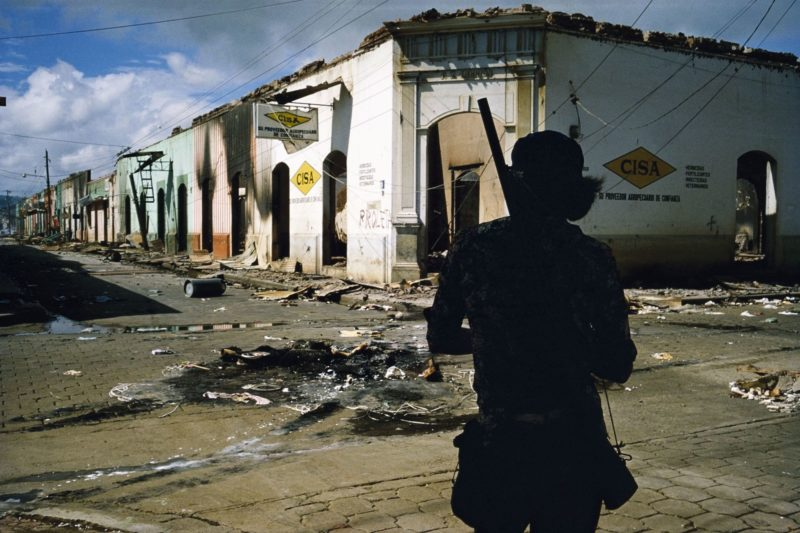 Susan Meiselas - Muchacho withdrawing from the commercial district of Masaya after three days of bombing, Masaya, Nicaragua