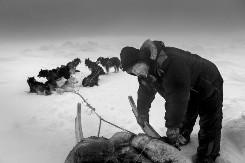 Ragnar Axelsson - Last Days of the Arctic - A hunter following polar bear tracks on the ice near Ittoqqortoormiit