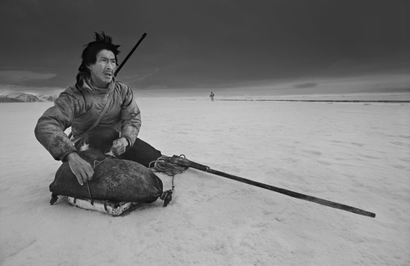 Ragnar Axelsson - Last Days of the Arctic - Hunter Ole Neylsen looking for a polar bear on the ice in Thule
