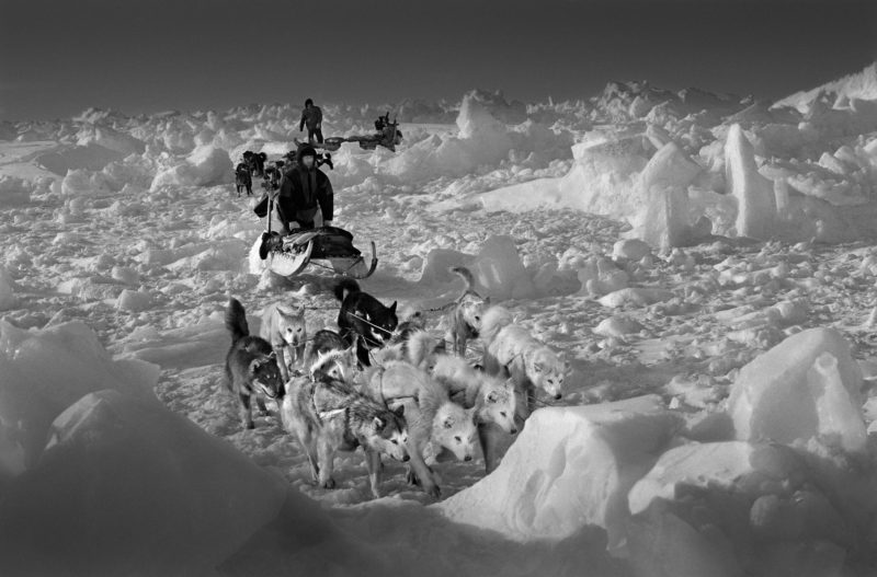 Ragnar Axelsson - Last Days of the Arctic - Polar bear hunters, Hjelmer and Isak, on rough packed ice on the east coast of Greenland. The temperature was minus 35 degrees