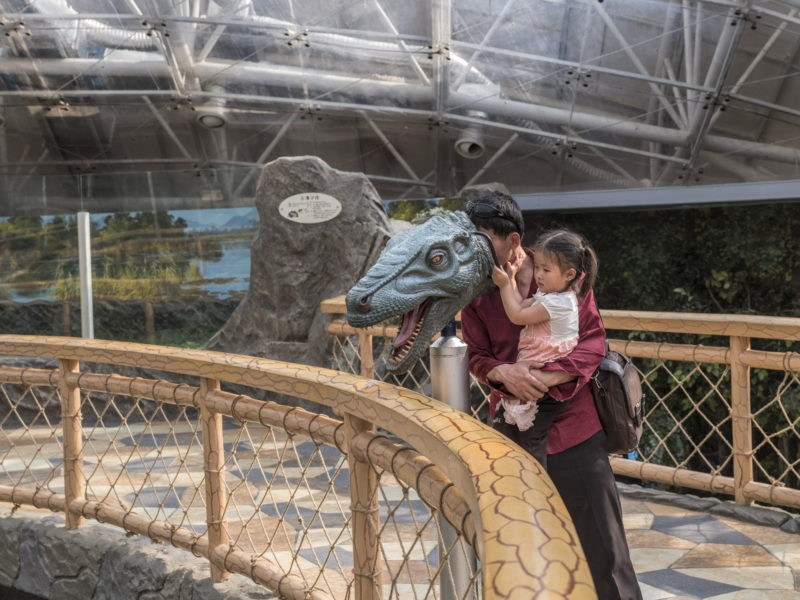 Carl De Keyzer - A man and his daughter learn about prehistoric life; Pyongyang Zoo. 28 May 2017 3.00 PM
