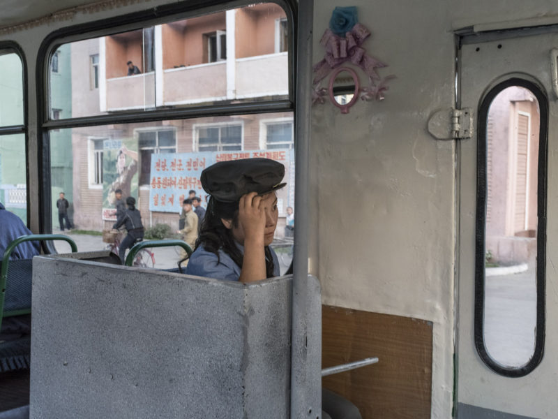 Carl De Keyzer - Chongjin, North Hamgyong Province. A trolley-bus attendant. While the number of cars, including taxis, has increased in recent years, city dwellers make extensive use of public transportation. 20 September 2015 5:00 PM