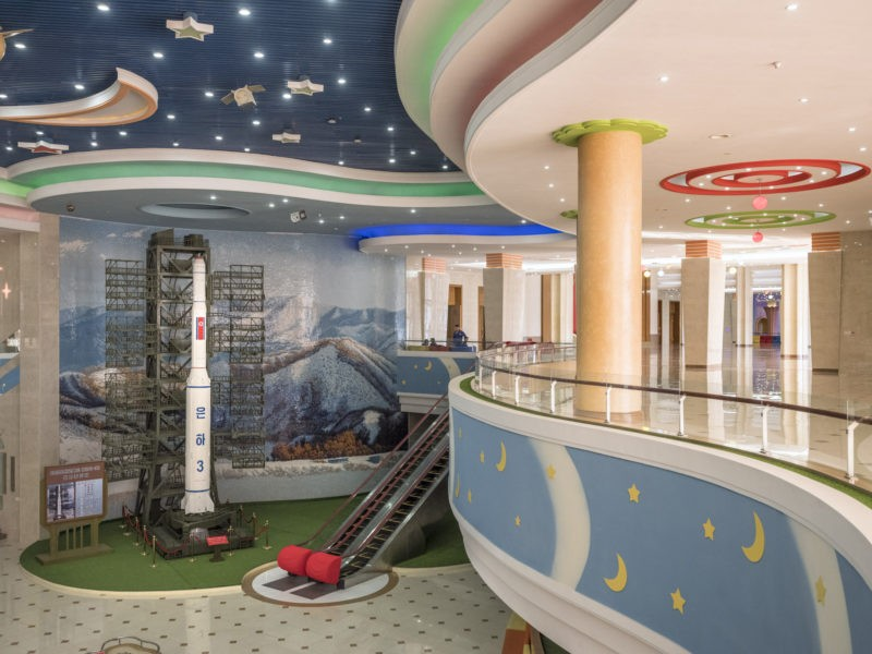 Carl De Keyzer - Interior of the recently renovated Manggyondae Schoolchildren's Palace. Pyongyang. The rocket is the Unha-3 (or 'Galaxy-3') carrier, designed to deliver payloads into space. 1 June 2017 4:00 PM