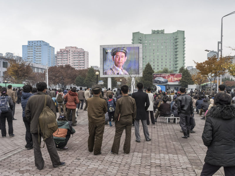 Carl De Keyzer - Pyongyang Station, Pyongyang. Locals and travelers watch a film on a public screen. This screen in the center of the city regularly shows movies throughout the day. It is also used for important news broadcasts, such as the announcement of nuclear or missile tests, for example. 9 November 2015 11:00 AM