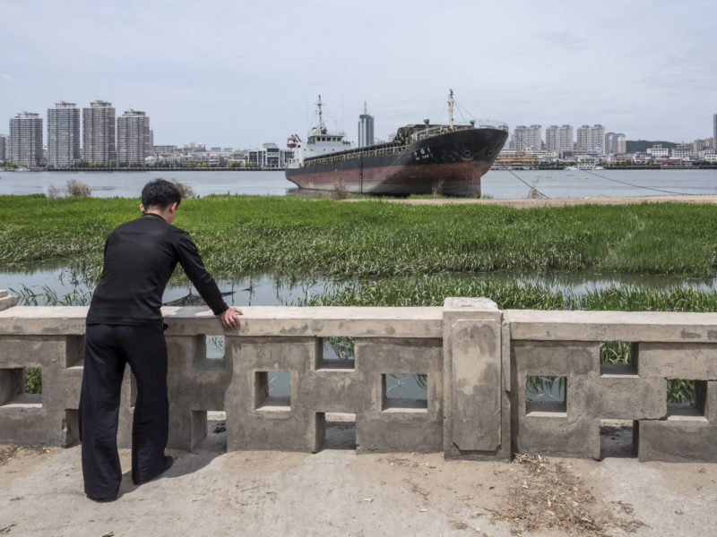 Carl De Keyzer - Sinuiju, North Pyong'an Province. Korean freighter moored on the Amnok (Yalu) River. Across the far bank is the Chinese city of Dandong, Liaoning Province. 9 June 2017 11:00 AM
