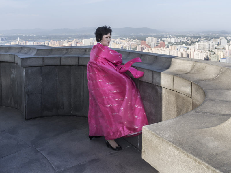 Carl De Keyzer - Tower of the Juche Idea, Pyongyang. Local guide and expert on the Pyongyang skyline, wearing traditional Korean dress. . 16 September 2015 4:00 PM